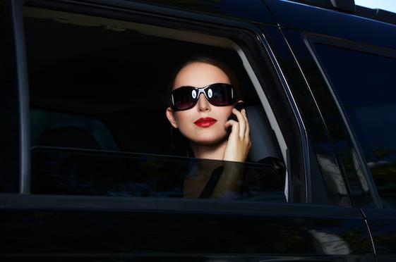 Femme conduite dans une berline avec chauffeur.